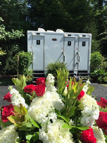 Renting a restroom trailer for your next outdoor party? Add flowers and flooring to create a showstopper